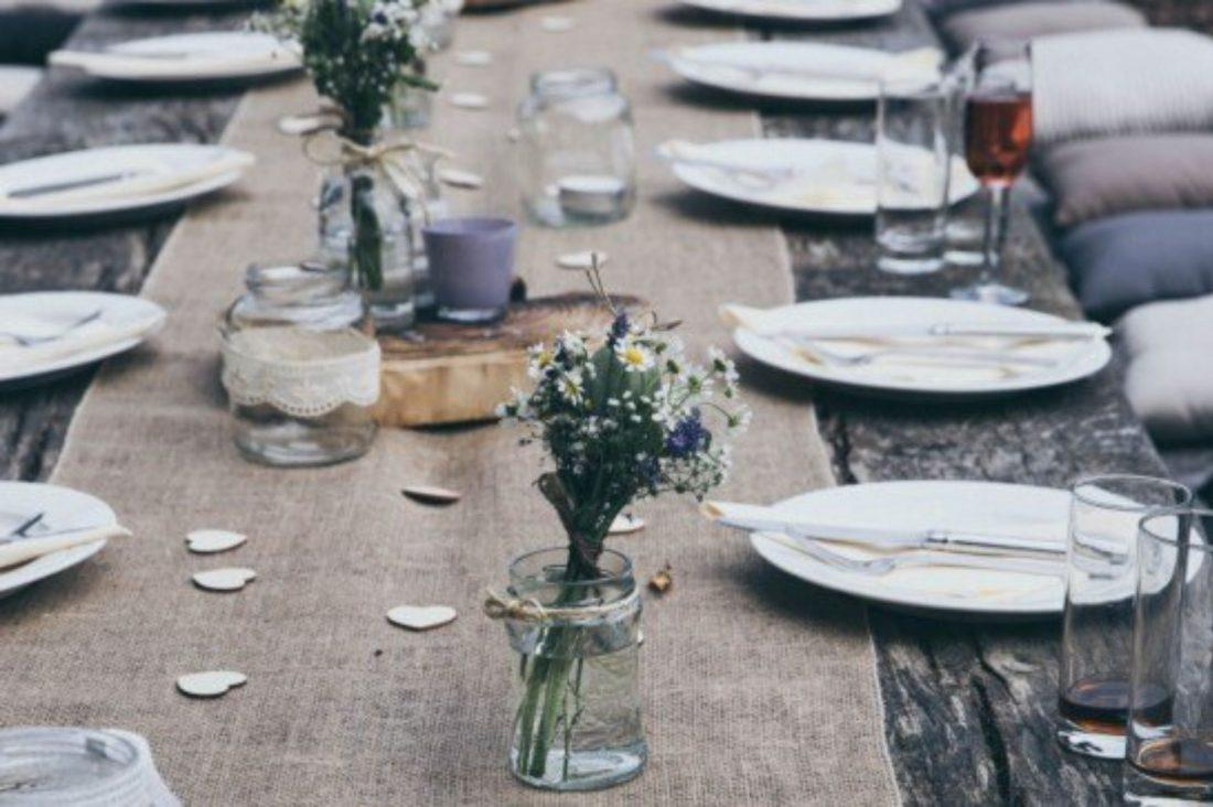 A dinign table laid with crockery and flowers