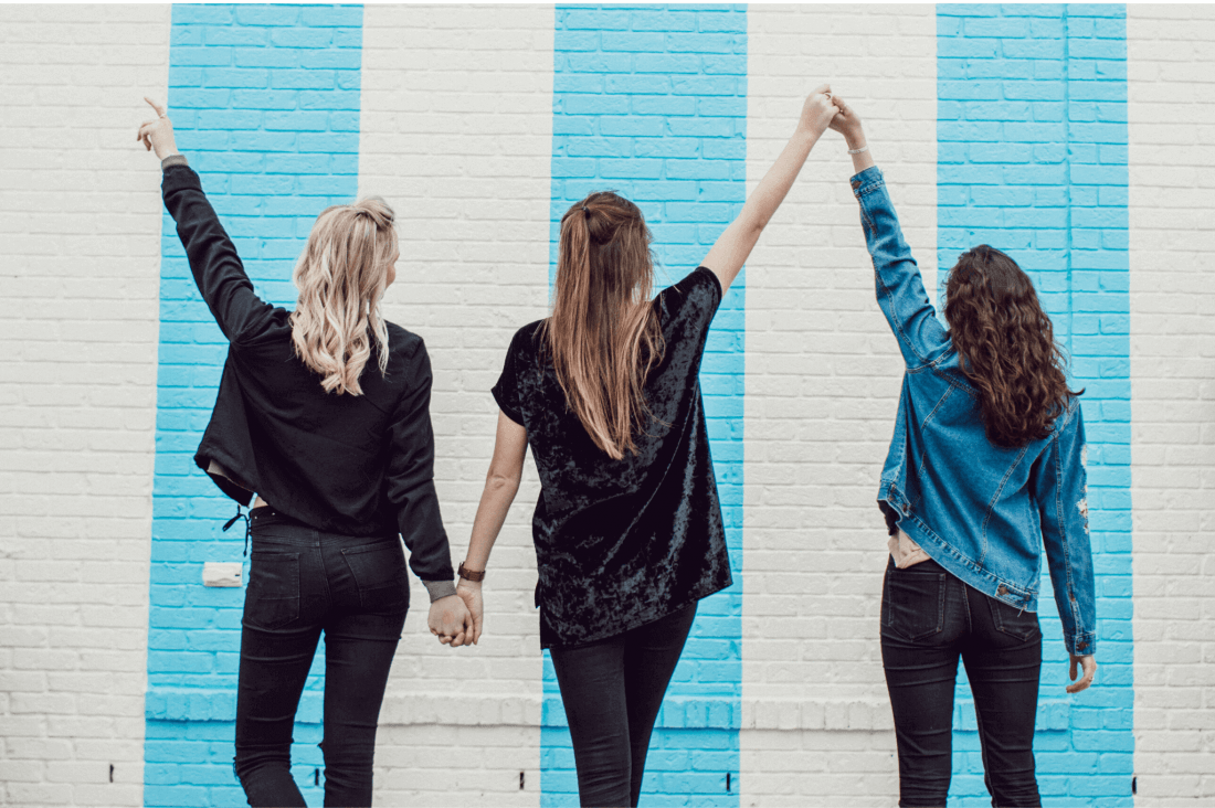 3 friends pose in front of a colourful wall